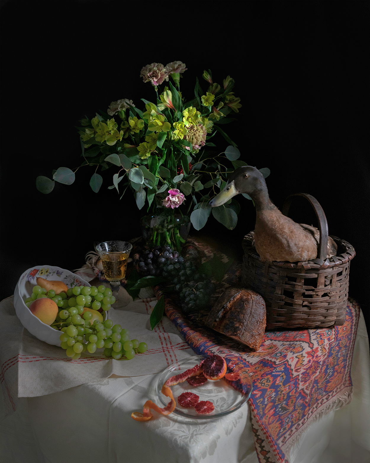 duck in basket on table with flowers and fruit